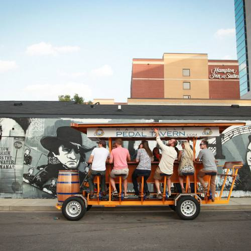 A group of Nashville Pedal Tavern riders in front of a downtown Nashville mural of Johnny Cash.