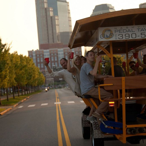 A Nashville Pedal Tavern tour group raising their glasses while riding, with downtown Nashville in the background.