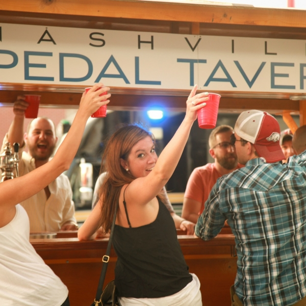 Two women toasting their cups as they ride the Pedal Tavern - nashville activities, nashville attractions